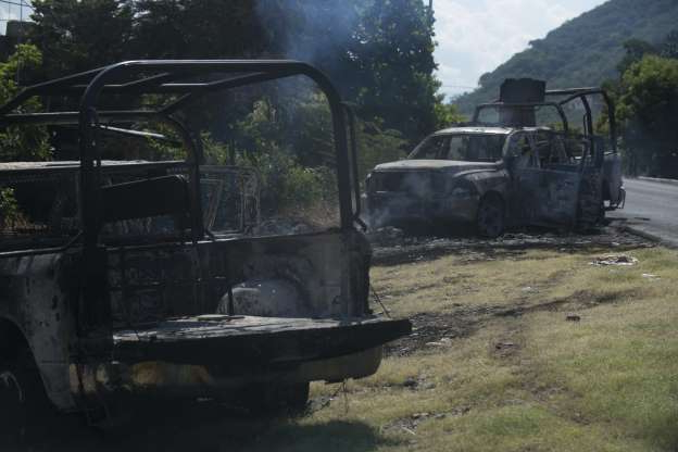 Slide 2 of 30: Charred trucks that belong to the Michoacan state police stand on the roadside after they were attacked in El Aguaje, Mexico, Monday, Oct. 14, 2019. At least 13 police officers were killed and nine others injured in the ambush. (AP Photo/Armando Solis)