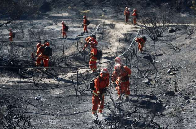 Slide 22 of 30: PORTER RANCH, CALIFORNIA - OCTOBER 12: An inmate firefighter crew from Prado Conservation Camp works to put out hot spots from the Saddleridge Fire on October 12, 2019 in Porter Ranch, California. Prado Conservation Camp is one of the 44 state prison fire camps where inmates perform firefighting duties during the wildland fire season for credit for early release and minimal pay. The wind-driven fire has burned 7,500 acres and destroyed 76 structures, leaving one dead.  (Photo by Mario Tama/Getty Images)