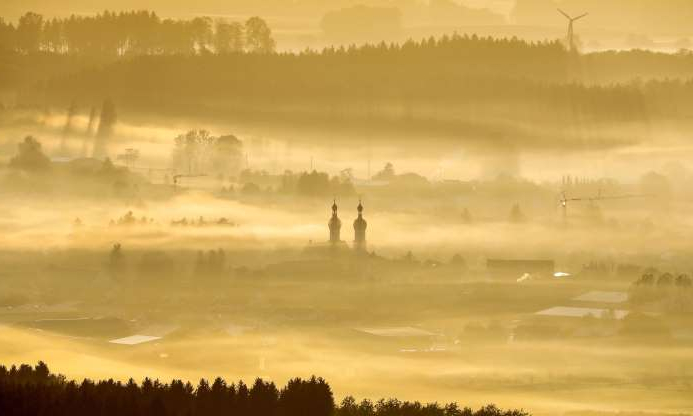 Slide 3 of 30: The St Simon and Judas church sticks out of the morning mist as sun rises in Uttenweiler, southern Germany, on October 14, 2019. (Photo by Thomas Warnack / dpa / AFP) / Germany OUT (Photo by THOMAS WARNACK/dpa/AFP via Getty Images)