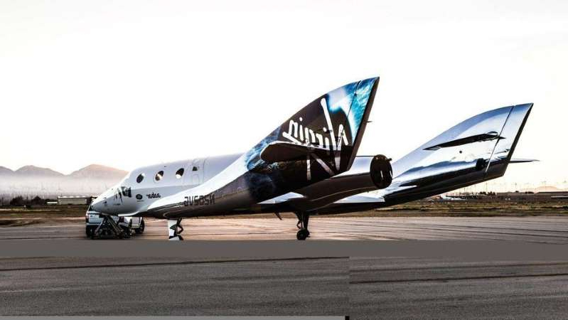a large passenger jet sitting on top of a runway: The iris of Stephen Hawking is printed on the side of Virgin Galactic's VSS Unity. Virgin Galactic