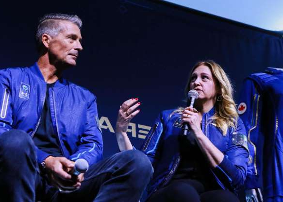 a man and a woman sitting on a stage: Beth Moses, chief astronaut instructor and interiors program manager for Virgin Galactic's SpaceShipTwo program, explained that the suits are designed for future astronauts to be able to savor the experience.