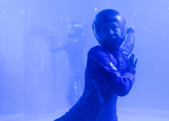 a man wearing a blue screen: Between the smoke and the dark and the speed of the dancing it was hard to get clear shots (no flash allowed of course). But note, the helmet is not part of the Virgin Galactic spacesuit -- it was just for the indoor skydiving performance.