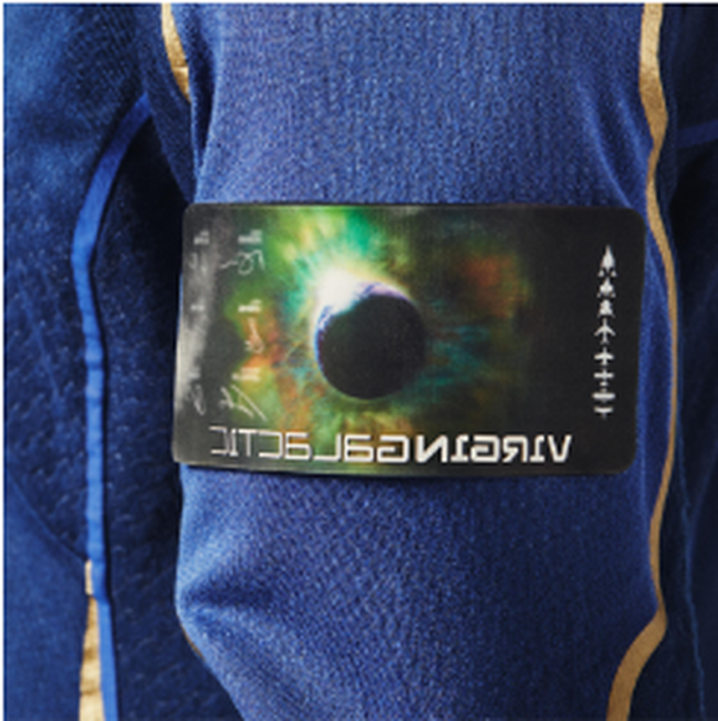 a person in a blue shirt: A mission patch is customized to be unique to every flight. Under Armour