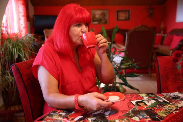 a person sitting at a table eating pizza: Zorica Rebernik, obsessed with the red color, drinks coffee in her house in the village of Breze near Tuzla