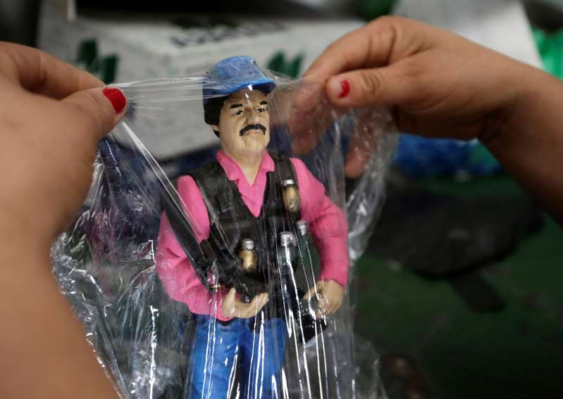 a person wearing a costume: A souvenir of Joaquin El Chapo Guzman is pictured in a store at the Saint Jesus Malverde chapel in Culiacan, in Mexico's state of Sinaloa. REUTERS/Daniel Becerril