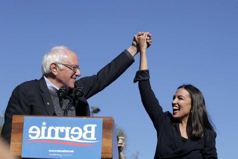 NEW YORK, NY - OCTOBER 19: Democratic presidential candidate, Sen. Bernie Sanders (D-VT) holds hands with Rep. Alexandria Ocasio-Cortez (D-NY) during his speech at a campaign rally in Queensbridge Park on October 19, 2019 in the Queens borough of New York City.  This is Sanders' first rally since he paused his campaign for the nomination due to health problems. (Photo by Kena Betancur/Getty Images)