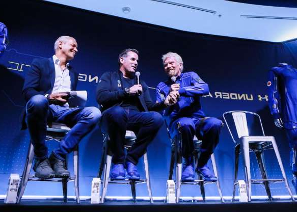Richard Branson, Kevin Plank sitting on a stage: Under Armour CEO Kevin Plank was on hand to discuss how the suits were made with eight commercial Under Armour technologies that address the challenges presented by space flight.