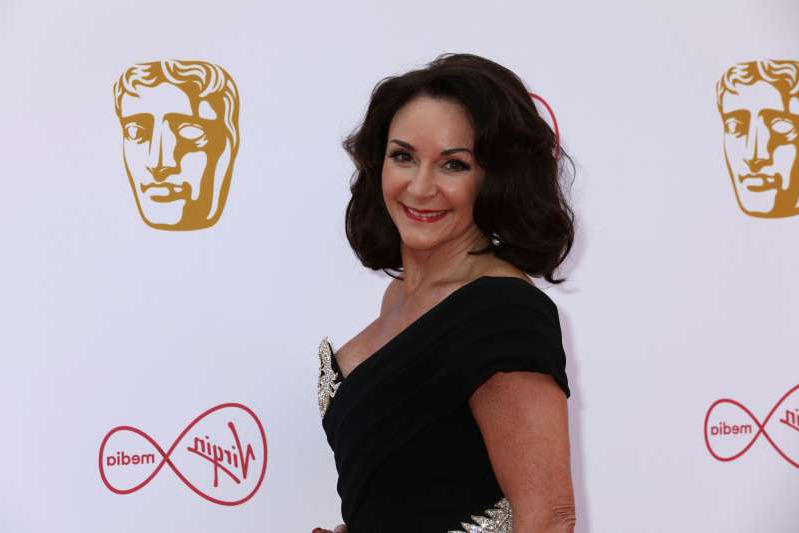 Shirley Ballas posing for a picture: Dance Coach Dame Shirley Ballas poses for photographers on arrival at the 2019 BAFTA Television Awards in London, Sunday, May 12, 2019.(Photo by Grant Pollard/Invision/AP)