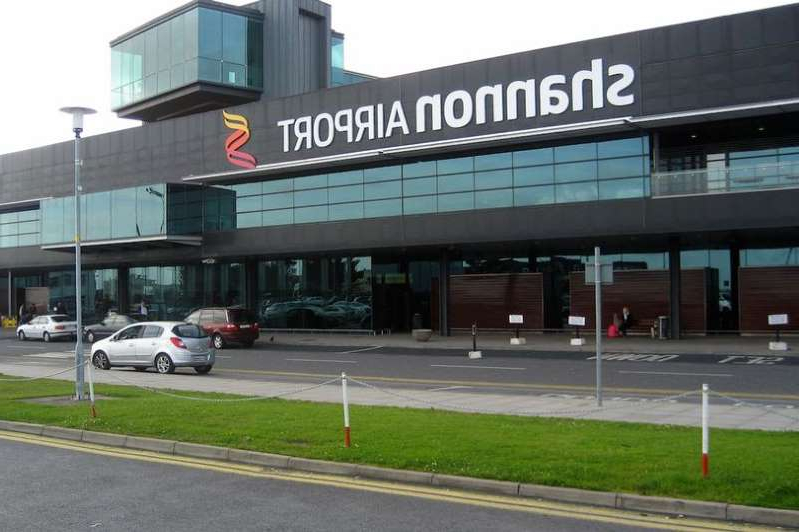 a building that has a sign on the side of a road: Shannon Airport