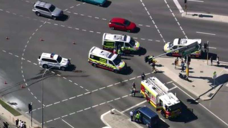 a car driving on a road: Paramedics treat the boy at the intersection of Narellan Road and Camden Valley Way.