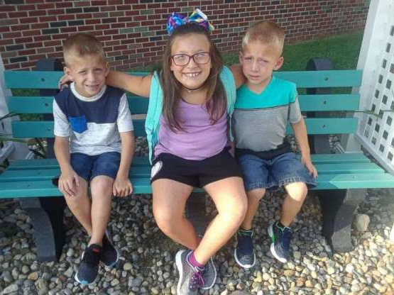 a group of young children sitting on a bench: Twin six-year-old brothers Mason and Xzavier Ingle are pictured with their nine-year-old sister Alivia Stahl in an undated family photo. The three were struck and killed by a car near Rochester, Ind., on Oct. 30, 2018.