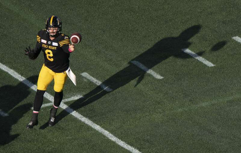 a person holding a football ball: Hamilton Tiger-Cats quarterback Dane Evans throws during first half CFL football game action against the Ottawa Redblacks in Hamilton, Ont. on Saturday,.
