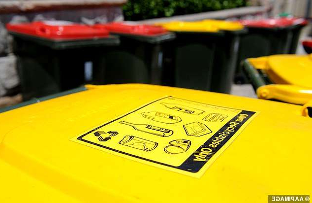 a yellow sign board of a car: Australians could be forced to separate their household waste into six garbage bins to address the country's recycling crisis
