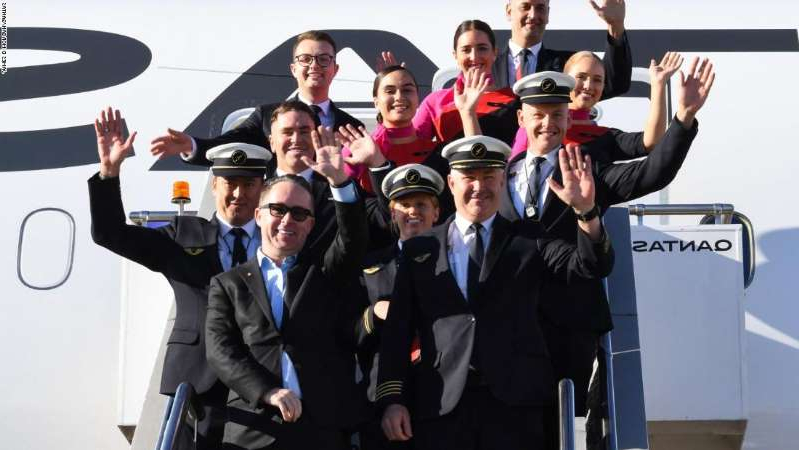 Alan Joyce et al. standing next to a man in a suit and tie: Crew on the Qantas flight from New York to Sydney