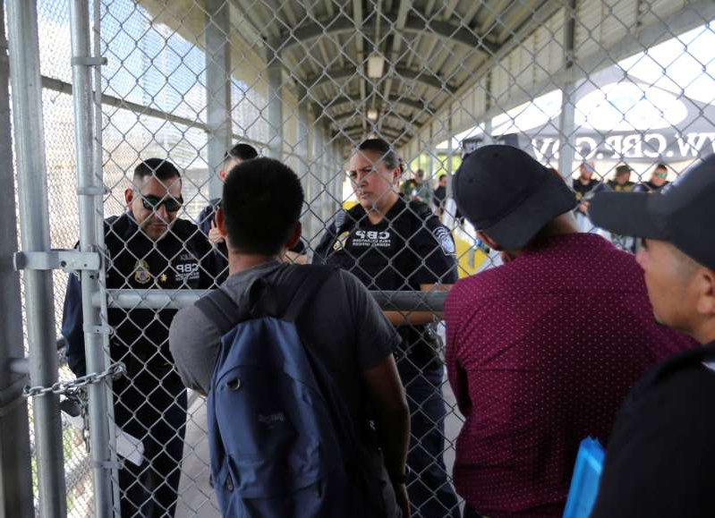 Migrants ask Customs and Border Protection officers when will the border re-open, after camping out on the Gateway International Bridge that connects downtown Matamoros, Mexico with Brownsville, Thursday, Oct. 10, 2019. Migrants wanting to request asylum camped out on the international bridge leading from Mexico into Brownsville, Texas, causing a closure of the span. (AP Photo/Fernando Llano)