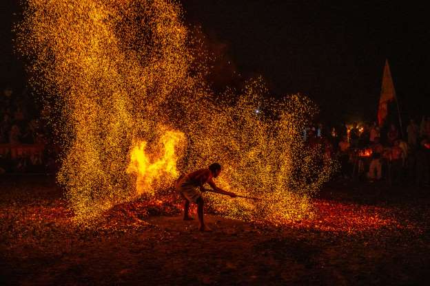 Slide 3 of 32: JINHUA, CHINA - OCTOBER 07: A barefooted man walks through burning charcoal as he performs 'Lianhuo', or 'fire walking' to celebrate the Double Ninth Festival on October 7, 2019 in Jinhua, Zhejiang Province of China. Double Ninth Festival is celebrated on the ninth day of the ninth lunar month, which falls on October 7 this year. (Photo by Yang Meiqing/VCG via Getty Images)