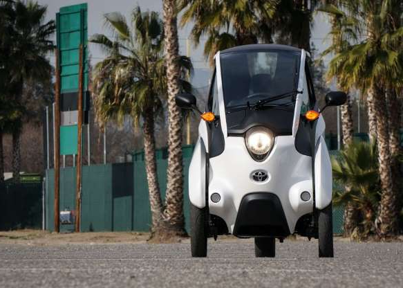 a bus parked in front of a palm tree: With its limited speed and range, the i-Road qualifies as a neighborhood electric vehicle in the US.