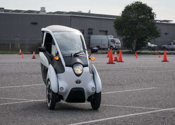 a car parked in a parking lot: The i-Road's lithium-ion electric battery gives it a range of 30 miles, ample for city distances.