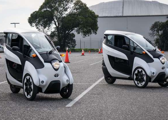a car parked in a parking lot: Toyota brought a couple of its i-Road electric vehicle prototypes to California to gauge public opinion. CNET took the opportunity for a ride.