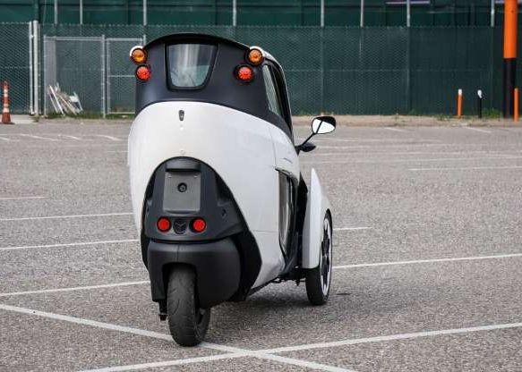 a car parked on the side of a road: The rear wheel turns, giving the i-Road a turning radius of about 9 feet.