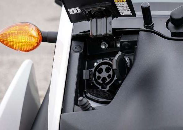 a close up of a car: The i-Road includes a standard J1772 electric-vehicle charging port.