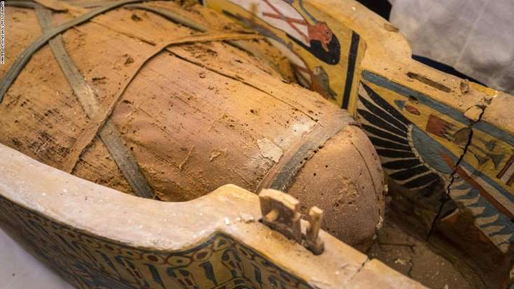 a close up of a dirty ground: An open coffin displayed in Luxor reveals a mummy.