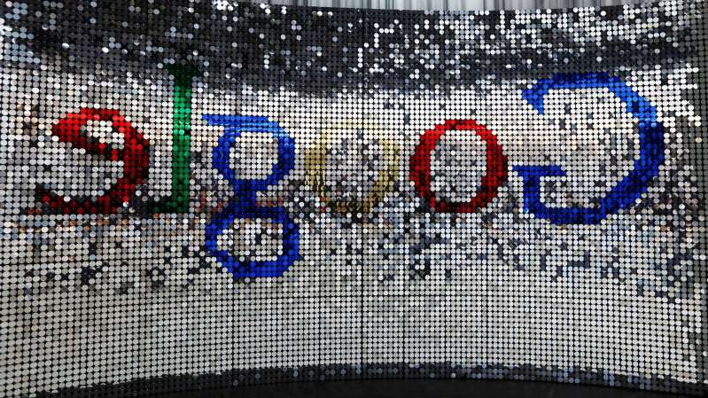 a close up of a fence: A sign featuring Google Inc.'s logo stands inside the entrance to their new U.K. headquarters at Six St Pancras Square in London.