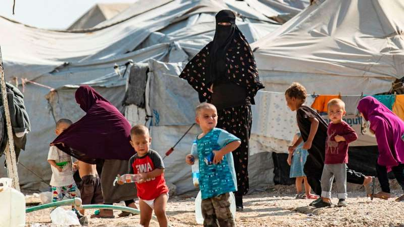 a group of people in a tent: Women look after children at the Kurdish-run al-Hol camp for the displaced where families of Islamic State (IS) foreign fighters are held
