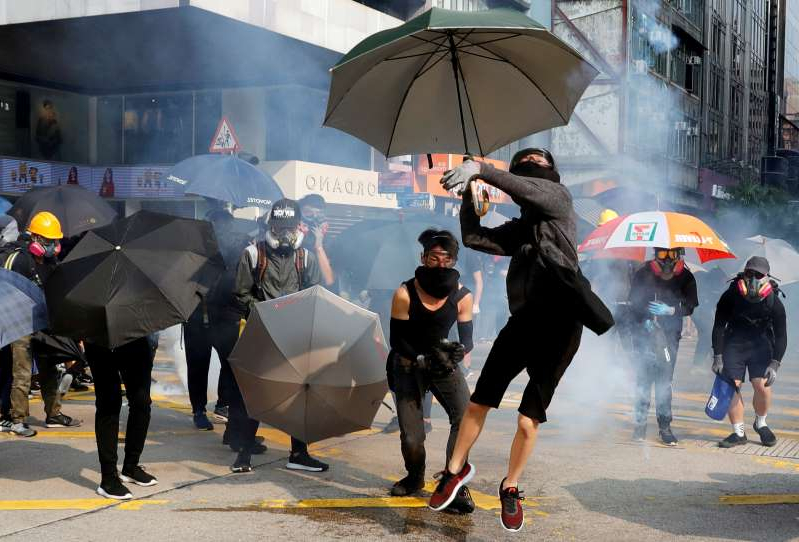 a group of people walking in the rain with an umbrella: Anti-government demonstrators attend a protest march in Hong Kong