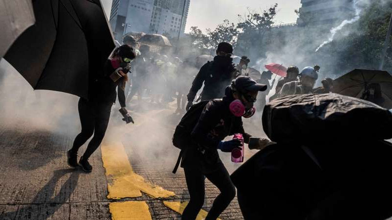 a group of people walking in the snow: The police fired tear gas during clashes with protesters in Tsim Sha Tsui on Sunday.