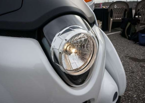 a motorcycle parked on the side of a car: The single headlight makes the i-Road a day and night driver.