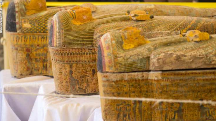 A photograph taken on October 19, 2019 shows sarchophagi displayed in front of Hatshepsut Temple in Egypt's valley of the Kings in Luxor - Egypt revealed today a rare trove of 30 ancient wooden coffins that have been well-preserved over millennia in the archaeologically rich Valley of the Kings in Luxor. The antiquities ministry officially unveiled the discovery made at Asasif, a necropolis on the west bank of the Nile River, at a press conference against the backdrop of the Hatshepsut Temple. (Photo by Khaled DESOUKI / AFP) (Photo by KHALED DESOUKI/AFP via Getty Images)