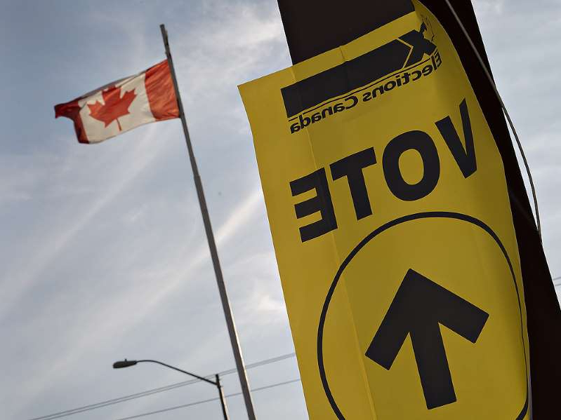 a sign in front of a flag: An Elections Canada sign directing voters to a voting location. (Postmedia file photo)