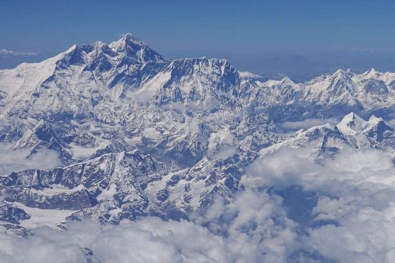 a view of a snow covered mountain: An aerial view of Mount Everest in April.