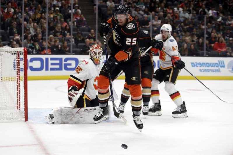 Anaheim Ducks' Ondrej Kase (25) jumps in front of the puck next to Calgary Flames goaltender Cam Talbot (39) during the second period of an NHL hockey game, Sunday, Oct. 20, 2019, in Anaheim, Calif. (AP Photo/Marcio Jose Sanchez)