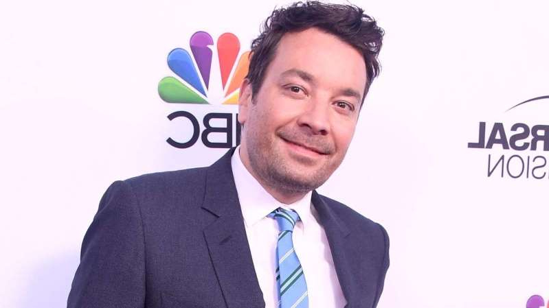 Jimmy Fallon wearing a suit and tie smiling at the camera
