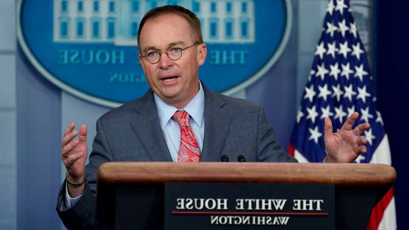 Mick Mulvaney wearing a suit and tie talking on a cell phone: Acting White House Chief of Staff Mick Mulvaney.