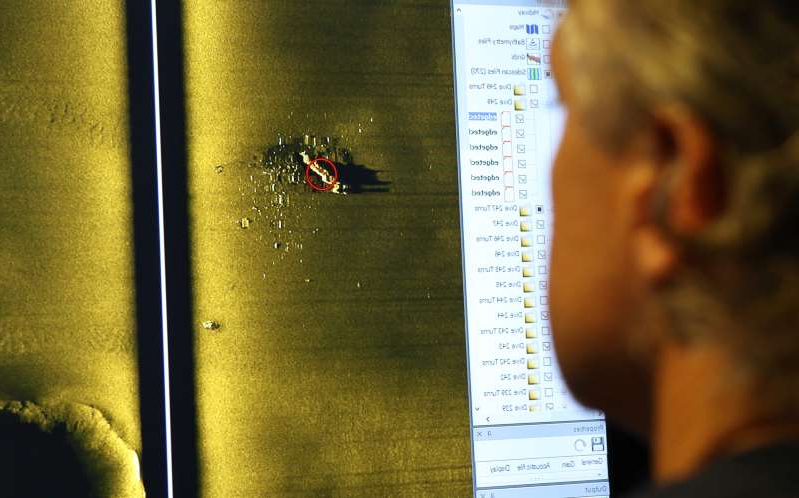 Rob Kraft, director of undersea operations at Vulcan Inc., reviews sonar scans of a warship from the World War II Battle of Midway that was found by his crew on the research vessel Petrel, Sunday, Oct. 20, 2019, off Midway Atoll in the Northwestern Hawaiian Islands. (AP Photo/Caleb Jones)