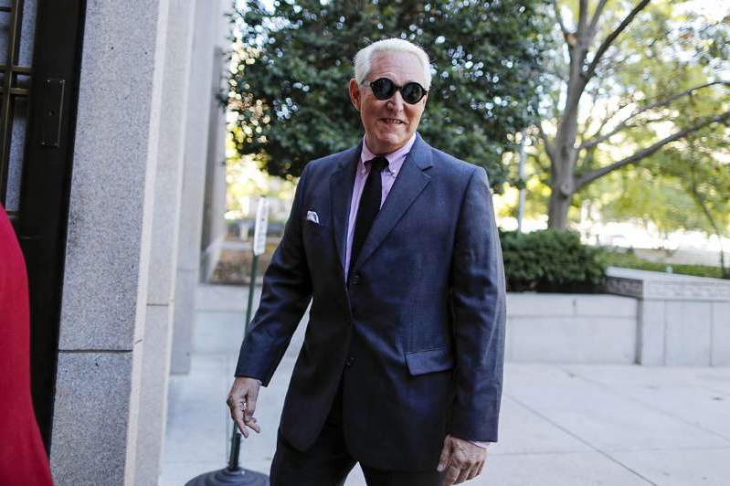 Roger Stone wearing a suit and tie walking on a sidewalk: Roger Stone.
