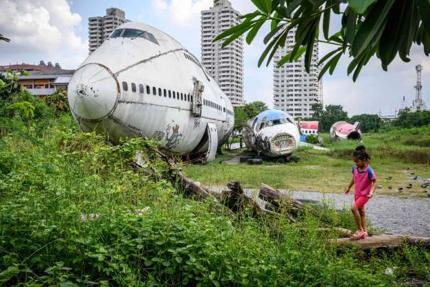 Slide 1 of 32: A child plays in front of abandoned aircraft in the suburbs of Bangkok on October 9, 2019. - The area, known as the