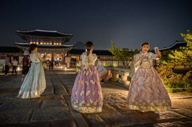 Slide 28 of 32: In a photo taken on October 4, 2019, visitors wearing traditional Korean hanbok dresses pose for photos during a night opening at Gyeongbokgung palace in central Seoul. (Photo by Ed JONES / AFP) (Photo by ED JONES/AFP via Getty Images)