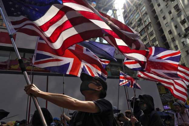 Slide 4 of 50: Protesters holding flags of the U.S. and Britain march toward the Tsim She Tsui police station during a rally in Hong Kong, Sunday, Oct. 20, 2019. Hong Kong protesters again flooded streets on Sunday, ignoring a police ban on the rally and demanding the government meet their demands for accountability and political rights. (AP Photo/Vincent Yu)