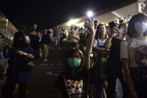 Slide 47 of 50: A Girl is seen holding up a candle light in Shueng Shui during a Vigil in Hong Kong on October 9, 2019, Pro-Democracy Protesters have been taken to the street of Hong Kong for Months in Protest of the government, the Protesters have five major demands including setting up an independent inquiry into police misconduct while handling recent protest in Hong Kong.