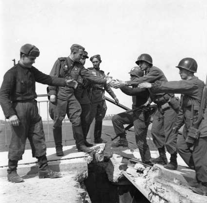 Slide 5 of 24: US troops of the 69th Infantry Division (left), shake hands with Russian troops in a staged photo on the wrecked bridge over the Elbe at Torgau, Germany, to mark the previous day's link-up between American and Soviet forces, 26th April 1945. Among the Americans are Bernard E. Kirschenbaum and Richard Johnson (second and third from left, respectively). The Soviet soldier in the centre is Lt. Charles Thau, a Pole drafted into the Soviet Army in 1943. (Photo by Allan Jackson/Getty Images)