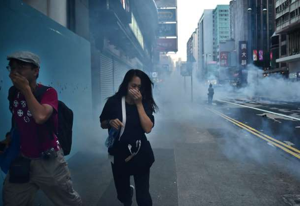 Slide 9 of 50: Protesters along Nathan Road react from tear gas fired by police during a pro-democracy march in the Kowloon district in Hong Kong on October 20, 2019. - Large crowds of Hong Kongers defied a police ban and began an illegal march on October 20, their numbers swollen by anger over the recent stabbing and beating of two pro-democracy protesters. (Photo by Ed JONES / AFP) (Photo by ED JONES/AFP via Getty Images)
