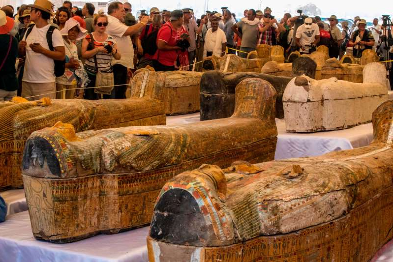 Tourists photograph sarcophagi displayed in front of Hatshepsut Temple in Egypt's valley of the Kings in Luxor on October 19, 2019. - Egypt revealed today a rare trove of 30 ancient wooden coffins that have been well-preserved over millennia in the archaeologically rich Valley of the Kings in Luxor. The antiquities ministry officially unveiled the discovery made at Asasif, a necropolis on the west bank of the Nile River, at a press conference against the backdrop of the Hatshepsut Temple. (Photo by Khaled DESOUKI / AFP) (Photo by KHALED DESOUKI/AFP via Getty Images)