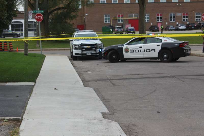 a car parked on a city street: Hamilton police on scene after an alleged fatal stabbing at Winston Churchill Secondary School on Oct. 7.