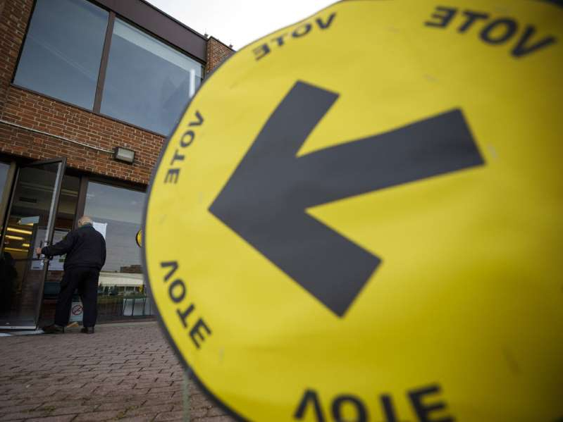 a close up of a sign: A resident enters a polling station in Toronto on Monday.