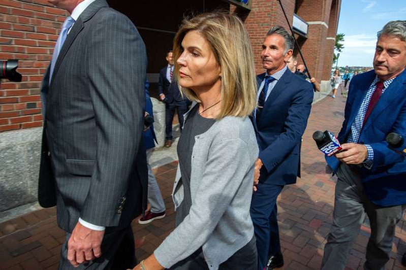 a group of people standing and talking on the phone: Actress Lori Loughlin and husband Mossimo Giannulli exit the Boston Federal Court house after a pre-trial hearing with Magistrate Judge Kelley at the John Joseph Moakley US Courthouse in Boston on Aug. 27, 2019.