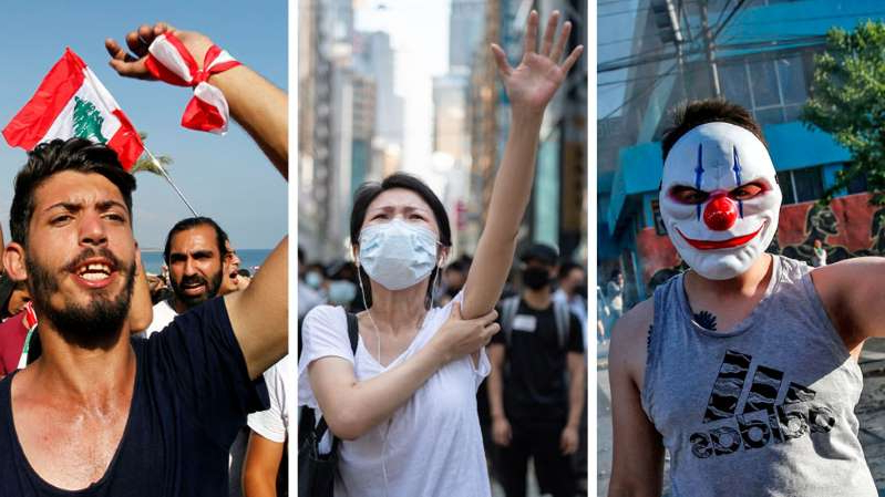 a group of people standing in front of a building: Protests have been taking place in Chile, Hong Kong and Lebanon